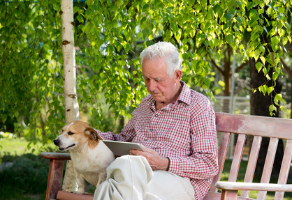 Senior Relaxing on Bench with Dog & Tablet