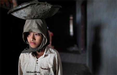 Young girl carrying cement for a new hotel in Burma